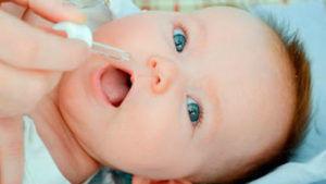 Вакцину закапывают в рот ребёнка